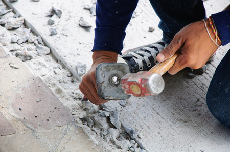 mason with chisel and hammer restores the concrete