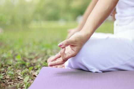 Mujer joven que hace yoga en el parque Foto de archivo