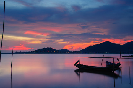 Beautiful silhouette fishing boat in lake at Twilight sky. photo