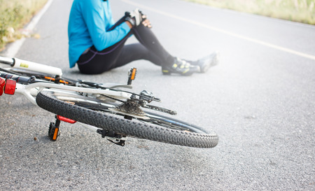 cyclist fell down from bike with injured knee joint sitting on floor. Stock Photo