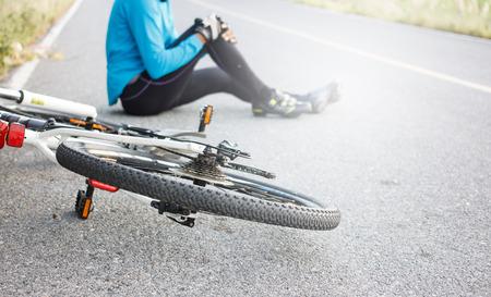 El ciclista se cayó de la bici con articulación de la rodilla lesionada sentado en el suelo. Foto de archivo