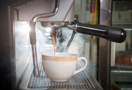 kafe: Espresso coffee machine, shot of espresso flowing into a cup.