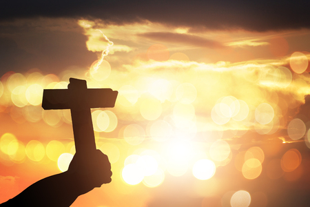 Silhouette human hands holding a cross holy and prayed for blessings from god. Amour worship god concept background.