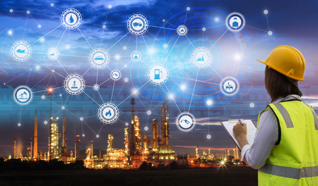 Industry 4.0 concept engineering use clipboard with checking and industrial icons on oil refinery industry sunset background. Banco de Imagens