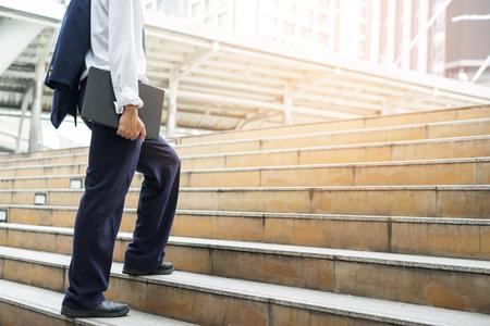 Businessman holding computer laptop walking up stairs to working. Horizontal outdoors shot. Stock Photo