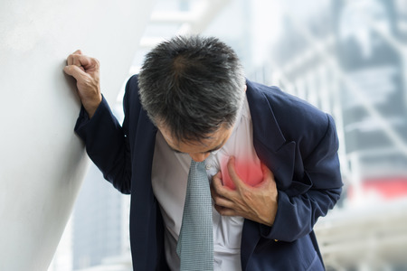 Business Man in uniform having heart attack / heartburn. acult pain possible heart attack. Stock Photo