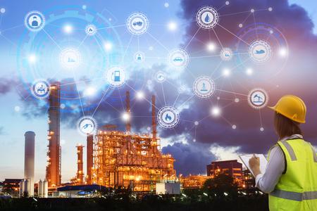 Industrie 4.0 concept gebruik klembord met het controleren en industriële pictogrammen op olie raffinaderij industrie zonsondergang achtergrond. Stockfoto