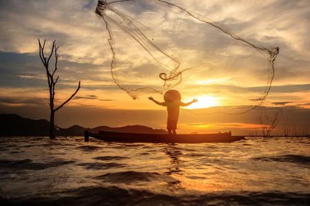 Pescador pescar con su red de pesca durante la puesta de sol.