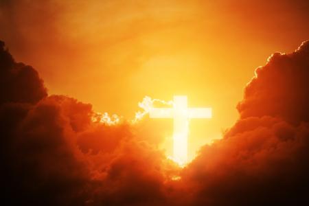 Conceptuele houten kruis of religie symbool vorm over een avondrood met wolken achtergrond voor God. geloof of opstanding van god en aanbidding christen.