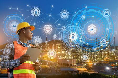 Geschäftsmannhände halten Tablet, das mit Nachtölraffinerie-Industrieanlagen- und -industrieikonen arbeitet. Fabrik in der Nacht als Kommunikation der Energie. Smarte Technologie 4.0 und Kommunikation