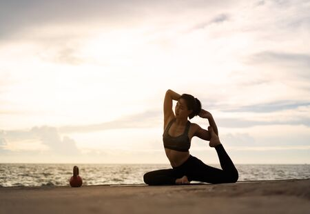 woman practicing yoga during surrealistic sunset at the seaside. healthy concept and workout. Reklamní fotografie