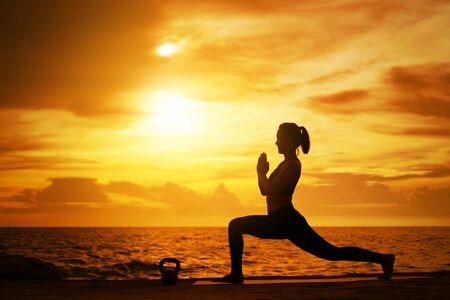 mujer practicando yoga durante la puesta de sol surrealista en la playa. concepto saludable y entrenamiento.