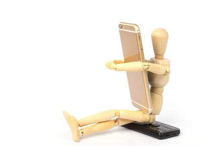 Wooden dummy grasping a new mobile smartphone in his arms and sitting on old phone mobile. transmission to new technology. 写真素材
