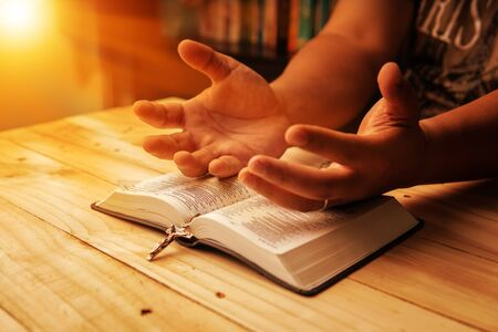 Christian hand while praying and worship for christian religion with blurred of her body background, Casual man praying with her hands together over a closed Bible. christian background. freedom. Stock Photo