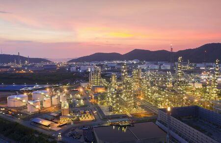Aerial view drone of oil storage tank with oil refinery factory industrial. Oil refinery plant at beautiful sky sunset and twilight. industry factory concept and transportation.