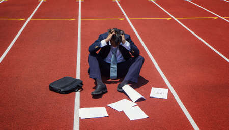 Business people are losing on the running track. Business failure and Economic crisis concept while documents were scattered on the ground. Business competition concept. Stockfoto