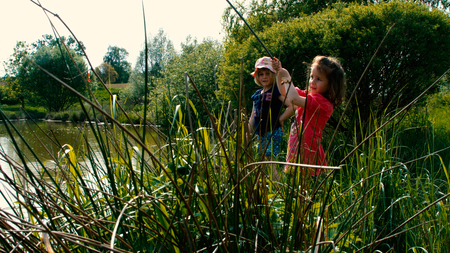 freetime activity: Two little girls go fishing together on a pond - part 4 Stock Photo