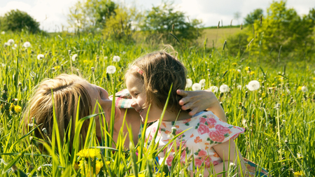 happy family nature: Mother and daughter are cuddling and playing together in a spring meadow - part 6 Stock Photo