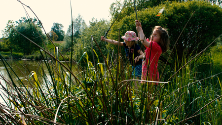 freetime activity: Two little girls go fishing together on a pond - part 5 Stock Photo