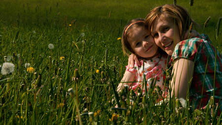 slumbering: Mother and daughter are cuddling in the evening light on a meadow - part 2