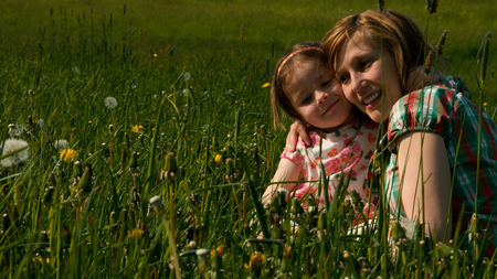 slumbering: Mother and daughter are cuddling in the evening light on a meadow - part 3