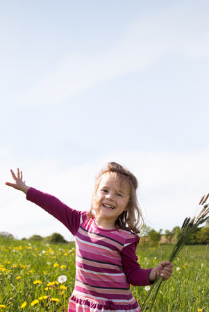 tuft: A little girl is flying with a tuft of grass over a spring meadow