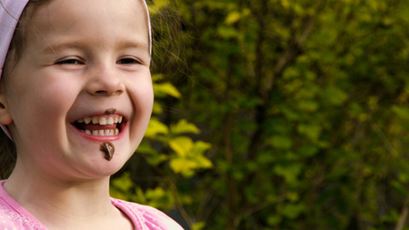 smeared: A little girl has been smeared with chocolate and laughs