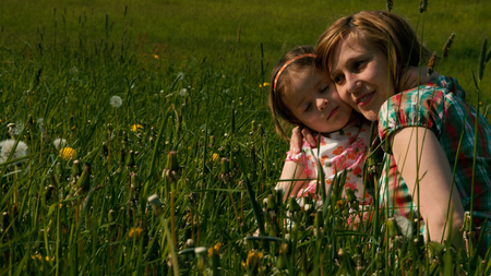 slumbering: Mother and daughter are cuddling in the evening light on a meadow - part 4