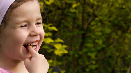 finger licking: A little girl licking chocolate cream from her finger and laughing - part 2 Stock Photo