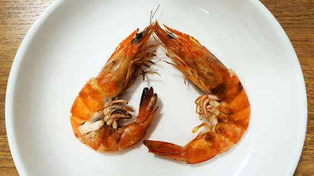 Heart shaped grilled shrimp on a white plate