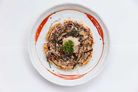 containing: Okonomiyaki is a Japanese savoury pancake containing a variety of ingredients.