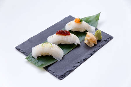 plato del buen comer: Torched Engawa Sushi Topping with Lime, Chilli Jam and Minced Daikon Served with Wasabi and Prickled Ginger on The Black Stone Plate. Foto de archivo