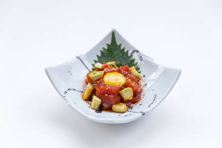 Diced Maguro (Bluefin Tuna) Salad with Diced Avocado and Egg Yolk Served on Japanese Ink Painted Ceramic Plate. Stock Photo