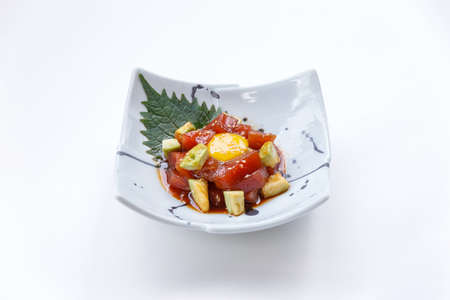 atun rojo: Diced Maguro (Bluefin Tuna) Salad with Diced Avocado and Egg Yolk Served on Japanese Ink Painted Ceramic Plate. Foto de archivo