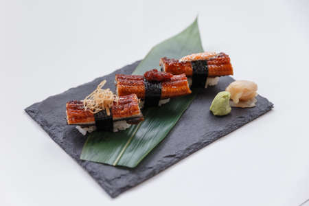 Grilled Unagi Sushi Set Topping with Katsuobushi, Chilli-Jam and Mayonnaise with Ebiko Served with Wasabi and Prickled Ginger on Black Stone Plate.