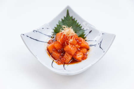 ceremic: Diced Raw Salmon Salad with Ikura (Salmon Roe) Topping with Katsuobushi Served on Japanese Ink Painted Ceremic Plate.