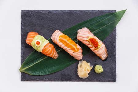 Torched und rohen Lachs Sushi-Set Topping mit Avocado, Mayonnaise und Ikura, Sauce und Käse mit Ebiko Serviert mit Wasabi und Ingwer prickelte auf Schwarz-Stein-Platte. Standard-Bild - 70385337