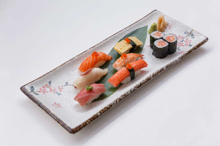 Sushi Set Include Maguro, Hamachi, Salmon, Kani, Shrimp, Tamagoyaki and Salmon Maki Roll Served with Wasabi and Prickled Ginger on Japanese Painted Stone Plate.