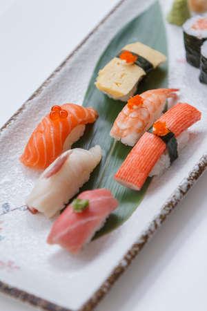 Sushi Set Include Maguro, Hamachi, Salmon, Kani, Shrimp, Tamagoyaki and Salmon Maki Roll Served with Wasabi and Prickled Ginger on Japanese Painted Stone Plate.