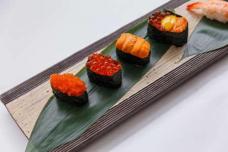 Sushi Set Include Tobiko, Ikura, Sea Urchin and Ikura, Urchin and Quail Egg Yolk Served on Leaf on Stone Plate. Stock Photo