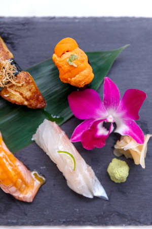 Premium Sushi Set Include Engawa, Hamachi, Hotate, Toro, Foie Gras, Salmon, Sea Urchin and Tai Served with Wasabi and Prickled Ginger on The Black Stone Plate. Stock Photo