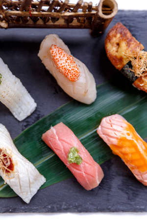 hotate: Premium Sushi Set Include Engawa, Hamachi, Hotate, Toro, Foie Gras, Salmon, Sea Urchin and Tai Served with Wasabi and Prickled Ginger on The Black Stone Plate. Stock Photo