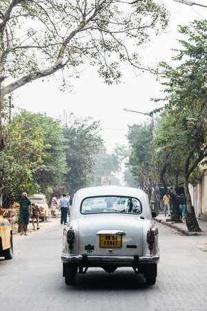 White classic car run on the street with trees in Kolkata, India