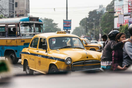 Yellow vintage taxi on the road in Kolkata, India