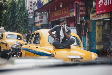 A man sit over the yellow vintage taxi on the street in Kolkata, India.