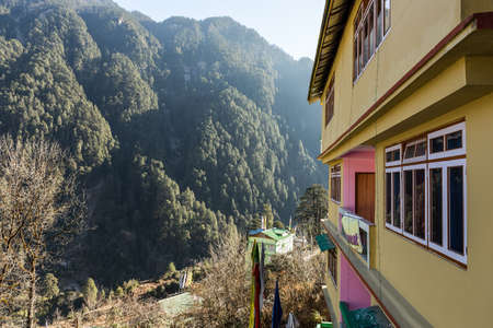 winter road: Hotel yellow wall and windows with green mountain landscape in hotel at Lachen. North Sikkim, India. Stock Photo