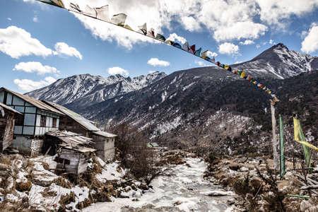 Zwarte berg met sneeuw op de top. Op de grond ligt een bevroren rivier met stenen, ijs, geel gras en Tibetaanse gebedsvlaggen in de Thangu en Chopta vallei in de winter in Lachen. Noord-Sikkim, India. Stockfoto