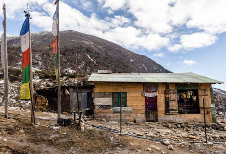 Rural grocery store. Wall made by weaving woods and door made by fabric with mountain in the background at Thangu and Chopta valley in winter in Lachen. North Sikkim, India.