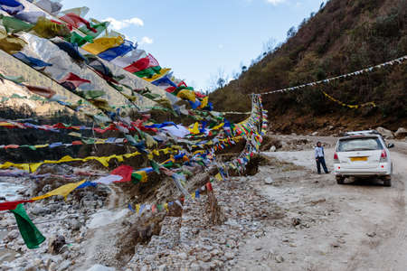 swaddled: Tibetan prayer flags waving and swaddled in sideway with white car over frozen river at Thangu and Chopta valley in winter in Lachen. North Sikkim, India.