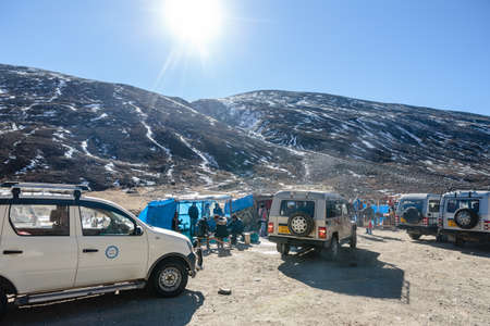 frozen lake: Four wheel drive cars parking area with tourists and floating market with Yunthang Valley in the background in winter in Zero Point at Lachung. North Sikkim, India.